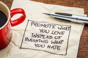 Promote what you love instead of bashing what you hate - handwriting on a napkin with cup of coffee